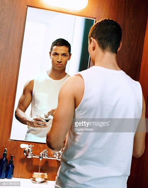 Young Man Stands in Front of a Bathroom Mirror Holding Shaving Foam and a Shaving Brush