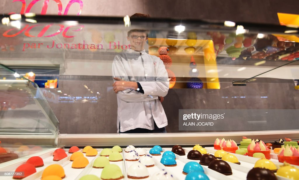 A young man stands in front of pastry on the 'Acide Macaron' stand, during the 'Europain fair', on February 6, 2016, in Villepinte near Paris. / AFP / ALAIN JOCARD