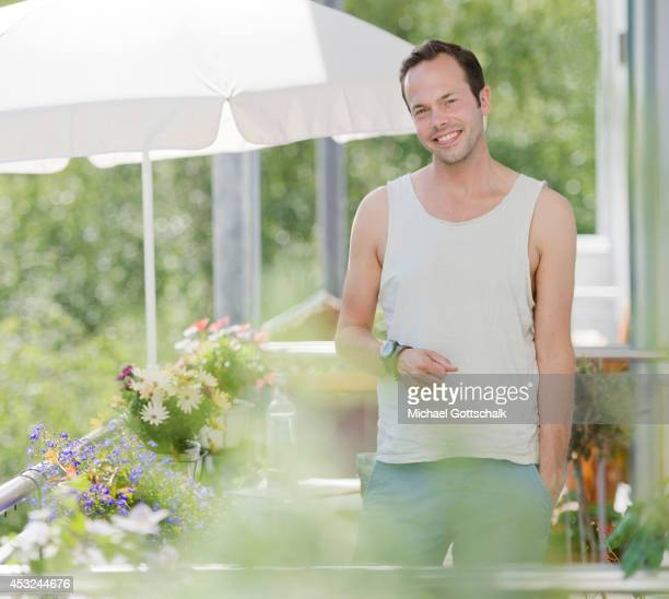 A young man stands next to his balcony flowers on his balcony on July 03 2014 in Berlin Germany