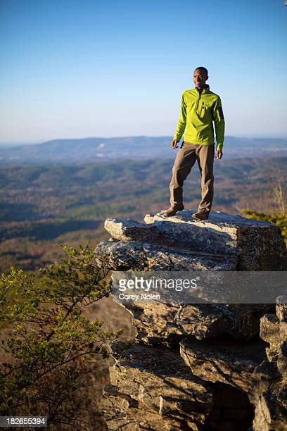 A young man stands on boulder on the edge of Mount Cheaha