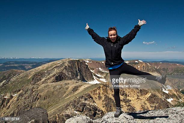 Young man stands on his one leg on top of mountain