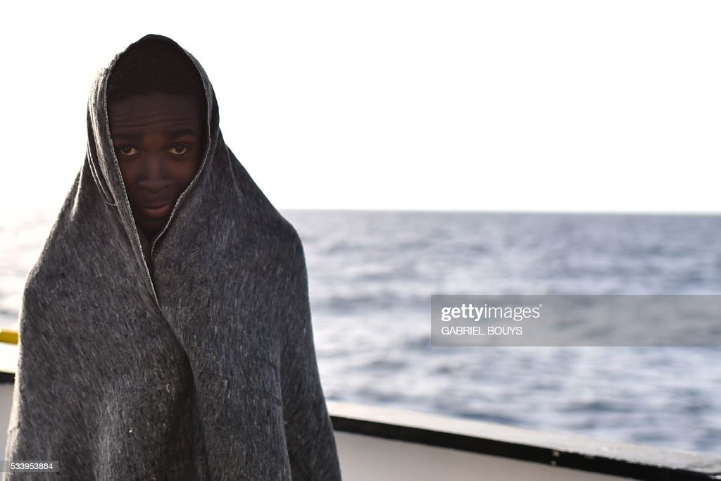 A young man stands wrapped in a blanket after a rescue operation of refugees and migrants at sea of the rescue ship 'Aquarius', on May 24, 2016 in front of the Libyan coast. The Aquarius is a former North Atlantic fisheries protection ship now used by humanitarians SOS Mediterranee and Medecins Sans Frontieres (Doctors without Borders) which patrols to rescue migrants and refugees trying to reach Europe crossing the Mediterranean sea aboard rubber boats or old fishing boat. / AFP / GABRIEL