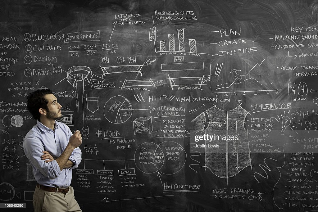 Young man staring at a chalkboard of options : Stock Photo