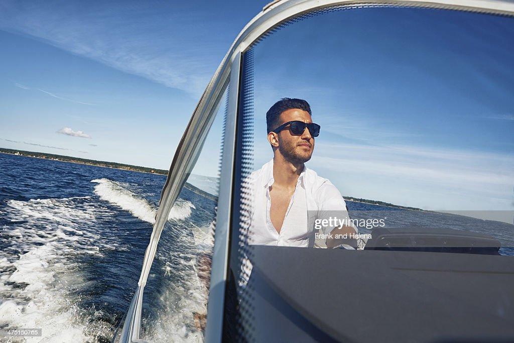 Young man steering boat, Gavle, Sweden