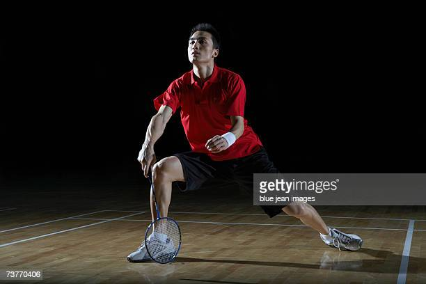 Young man steps to his right and prepares to return a shot during a game of badminton.