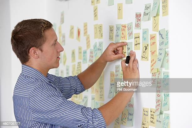 Young man sticking adhesive note on wall