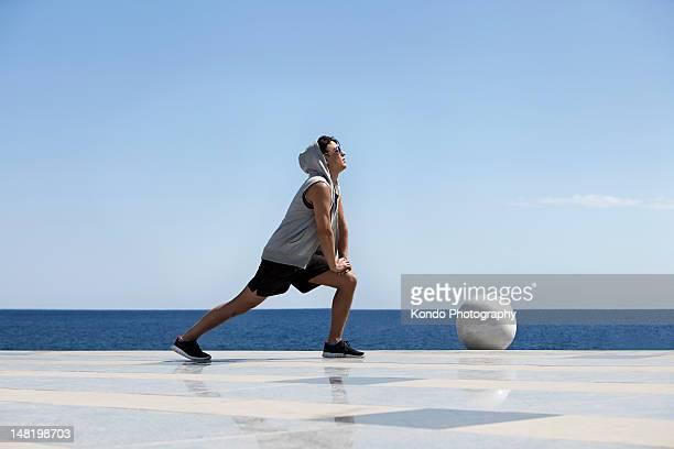 Young man stretching near ocean
