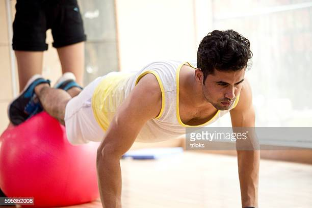 Young man stretching on fitness ball