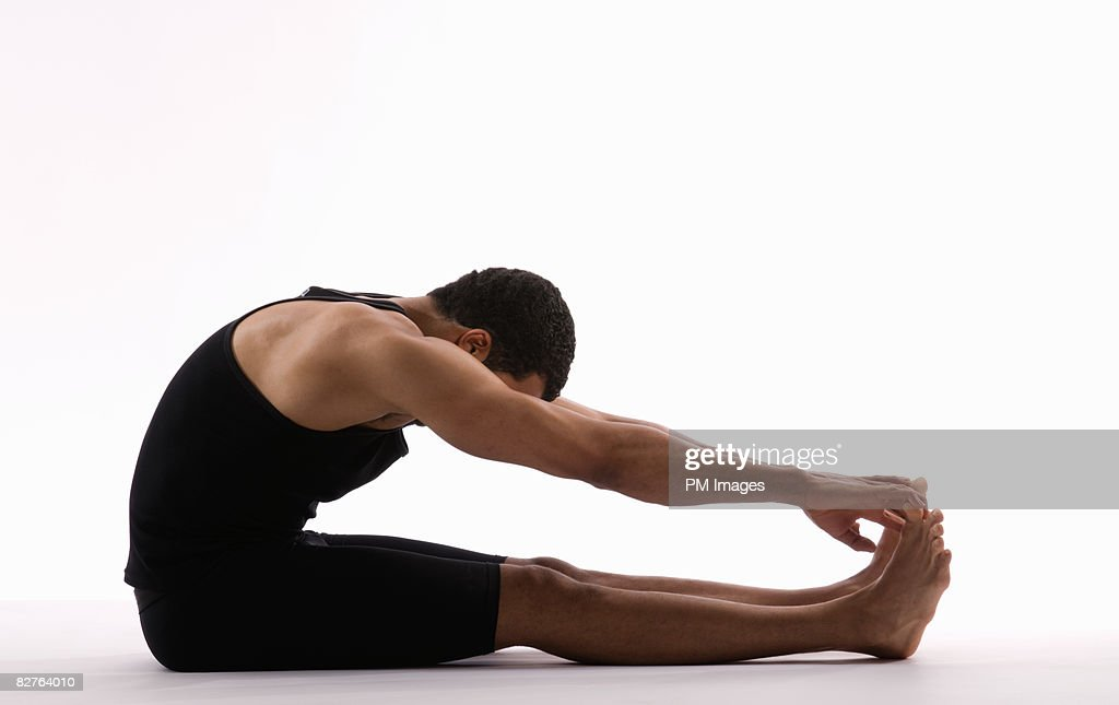 Young man stretching on floor, touching toes : Stock Photo