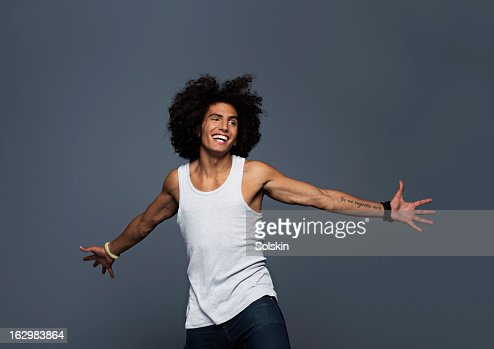 Young man stretching out arms, studio background