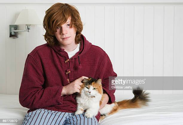 Young man stroking cat