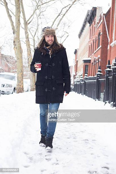 Young man strolling along snow covered street drinking takeaway coffee