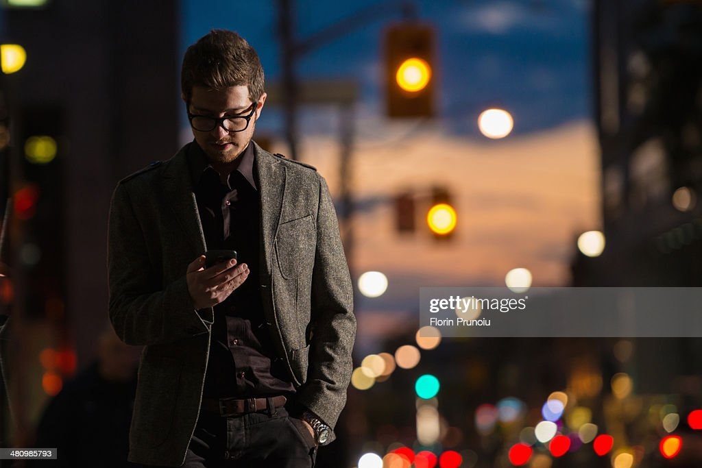 Young man strolling down street looking at mobile phone, Toronto, Ontario, Canada : Stock Photo