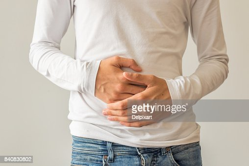 Young man suffering from stomach ache, diarrhea, constipation, acid reflux, indigestion, nausea : Stock Photo
