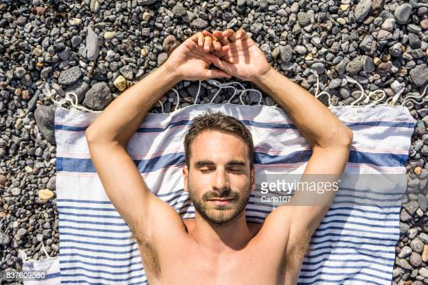 Young man sunbathing on a beach of stones