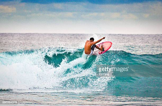 Jeune homme de surf surfer sur la plage de Kauai, Hawaï