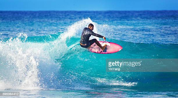 Joven hombre surfista surf en la playa de Kauai, Hawai