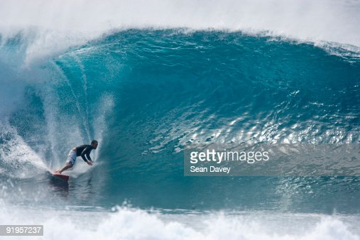 A young man surfing a big wave at Pipeline, on the north shore of Oahu, Hawaii.