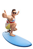 Young man surfing and making a thumb up gesture isolated on white background