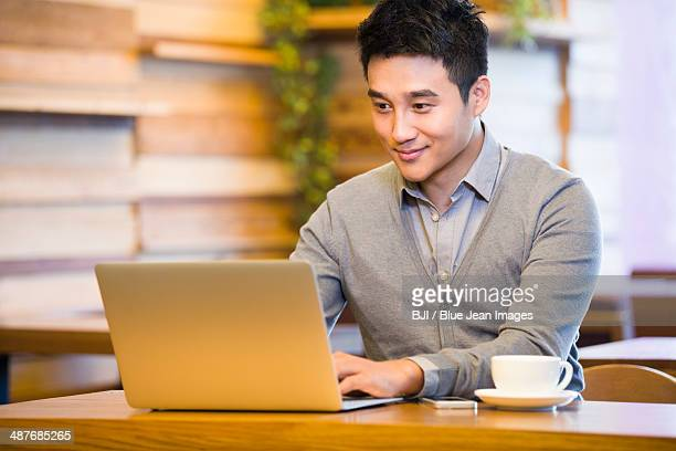 Young man surfing the net in coffee shop