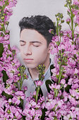 Young man surrounded by flowers