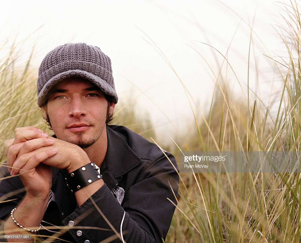 Young man surrounded by tall grass, hands clasped, portrait : Stock Photo