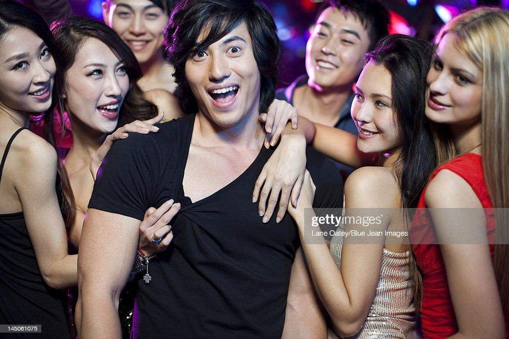 Young man surrounding by beautiful women in nightclub