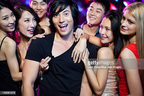 Young man surrounding by beautiful women in nightclub