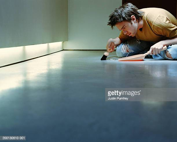 Young man sweeping floor with dust pan and brush