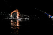Professional swimmer training the front crawl stroke in the racing pool.