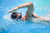 Young man swimming the front crawl in a pool, wearing swimming glasses
