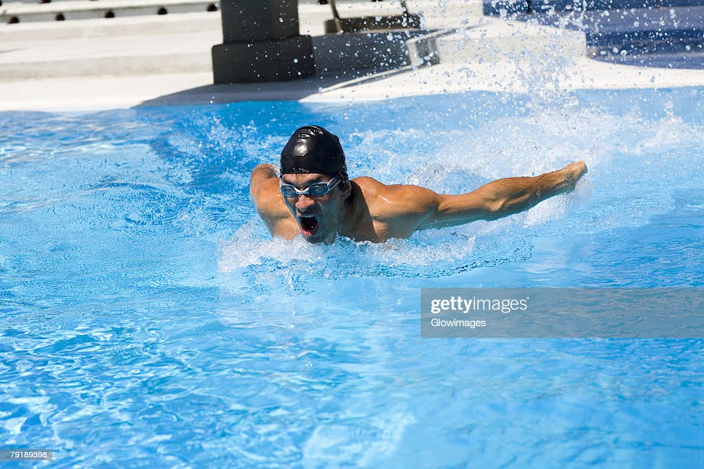 Young man swimming the butterfly stroke in a swimming pool : Stock Photo