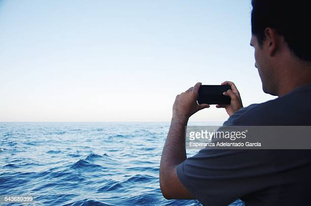 Young man take a picture with a smartphone to the sea