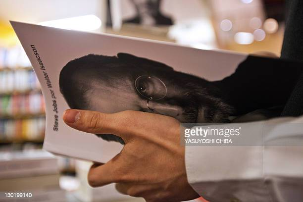 A young man takes a biography of the late 'Apple' cofounder Steve Jobs at a bookshop in Sao Paulo Brazil on October 24 2011 The eagerly awaited...