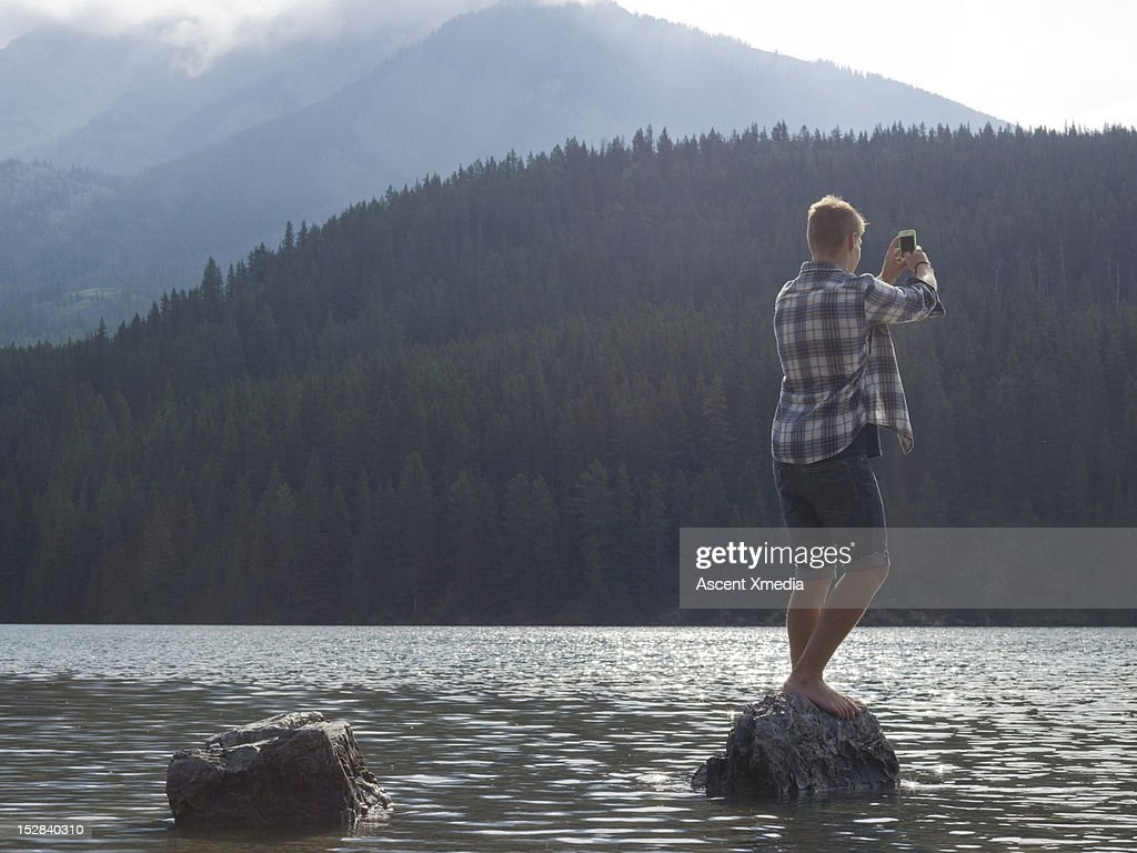 Young man takes cell phone pic, mtn lake : Stock Photo