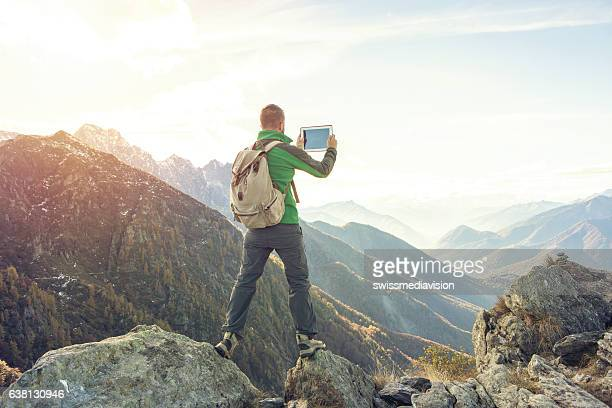 Young man takes digital tablet picture on mountain top