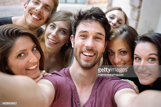 Young man takes his selfie. Group of smiling friends behind