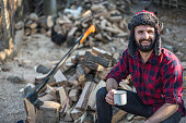 Young bearded lumberman sitting on the wood logs with a cup of coffee