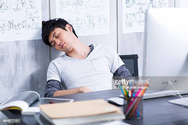 Young man taking a nap in the office
