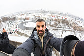 Young man taking a selfie in Budapest with snowy cityscape on background. He is wearing warm clothes and holding the camera with both hands. Travel, lifestyle  and seasons concepts.