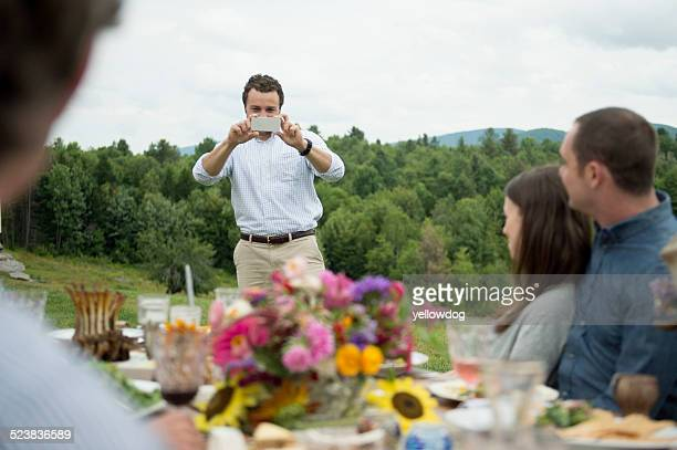 Young man taking photograph of family during meal, outdoors
