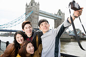Young man taking photograph of  friends by Tower Bridge, London, England