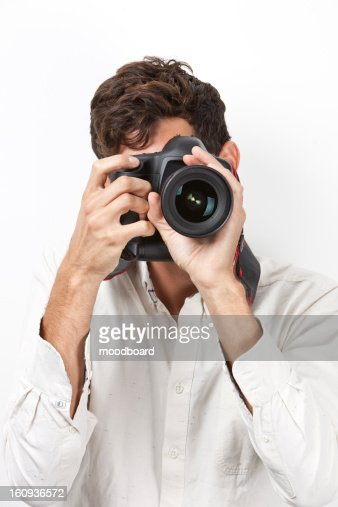 Young man taking photograph with retro style camera against white background : Foto de stock