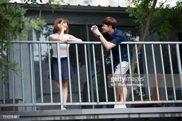 Young man taking photos of smiling girlfriend