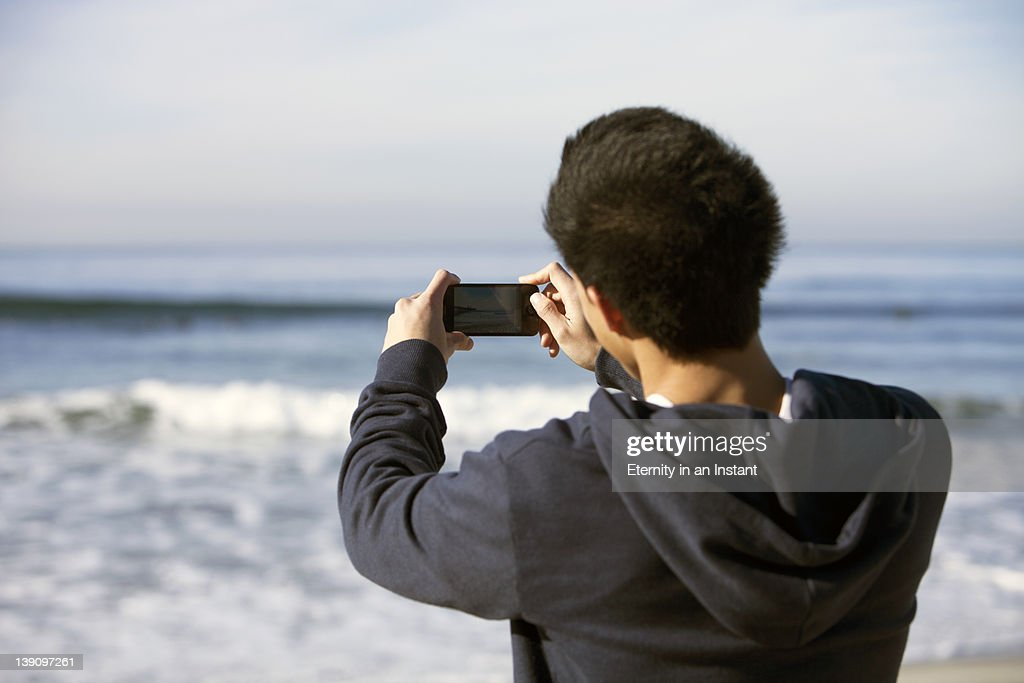 Young man taking photo,video with smart phone : Stock Photo