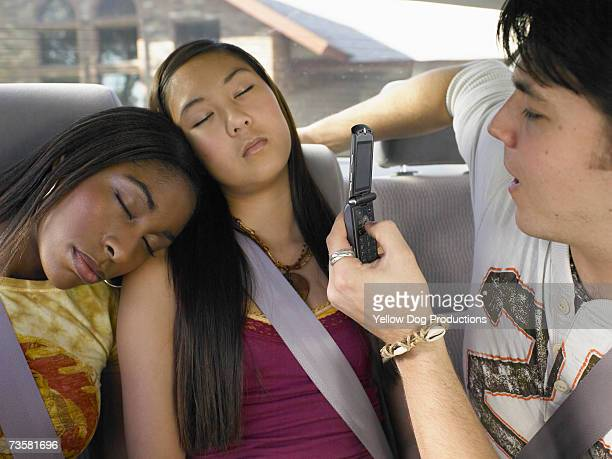 Young man taking picture with mobile phone of young woman and teenage girl (16-17) sleeping in car