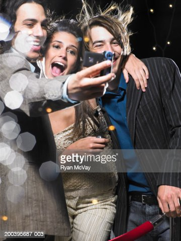 Young man taking self portrait with young woman and man, behind rope : Stock Photo
