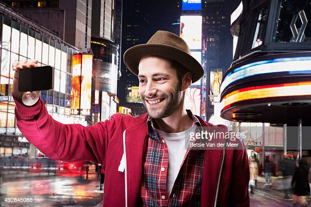 Young man taking selfie in city square at night.