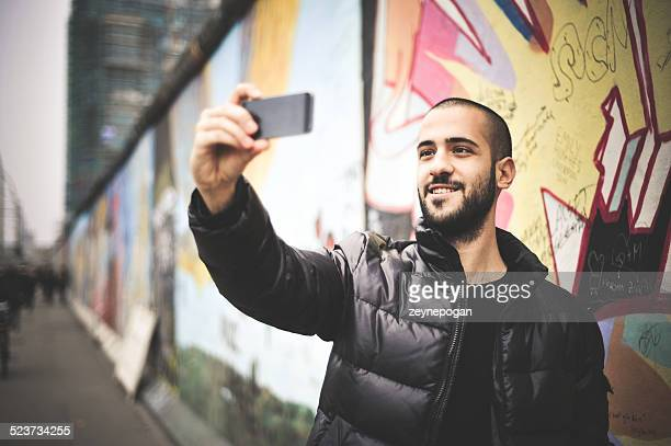 Jovem homem a tirar uma Selfie em frente ao Muro de Berlim