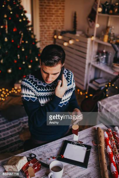 Young man talkin with his mom on the phone, while wrapping gifts